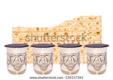 Half of a broken matzah behind 4 shiny silver kiddush cups filled to the brim with red wine for the Passover seder. Room for text. Isolated on a white background. - stock photo