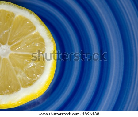Half of a lemon on a blue swirl plate - stock photo
