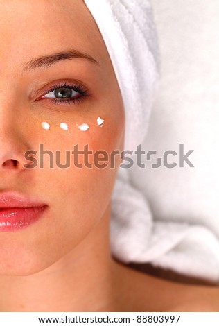 Half of a woman's face with moisturizing cream under the eye - stock photo