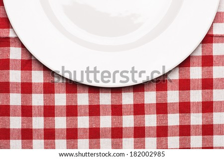 Half of composition plate at classic checkered tablecloth - stock photo