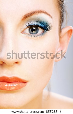 Half of face beautiful young woman with bright faultless make-up. - stock photo