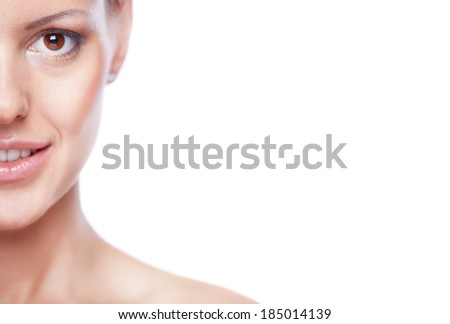 Half of face of a young adorable woman looking at camera  - stock photo