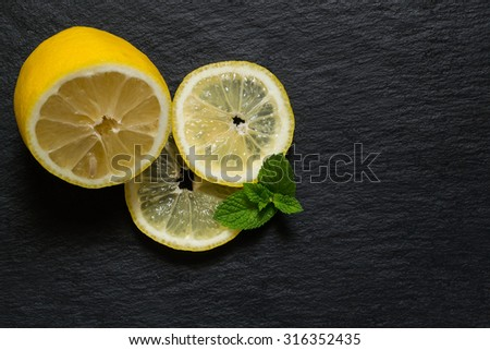 Half of fresh juicy lemon, slices and mint leaves on a slate board - stock photo