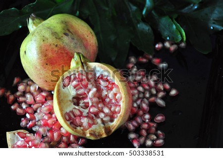Half of fresh pomegranate with seed on black background