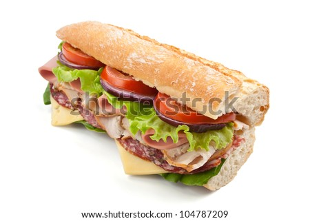 half of long tasty subway baguette sandwich with lettuce, tomatoes, ham, turkey breast, salami and cheese isolated on white background - stock photo