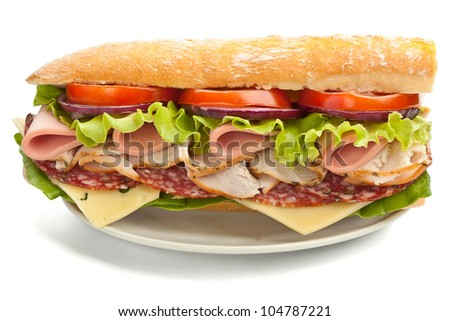 half of long tasty subway baguette sandwich with lettuce, tomatoes, ham, turkey breast, salami and cheese on cutting board with ingredients - stock photo