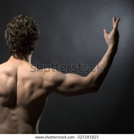 Half of one handsome sexy strong muscular young man with bare back and curly hair standing with raised hands indoor in studio on black background, square picture