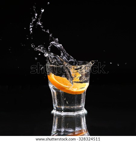 Half of orange falling down in glass with water on deep black. Beautiful glass with sparkling water or other transparent drink and a slice of lemon on black background - stock photo