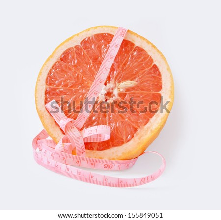 Half of red grapefruit with centimeter on a white background