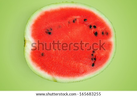 Half of watermelon on green background