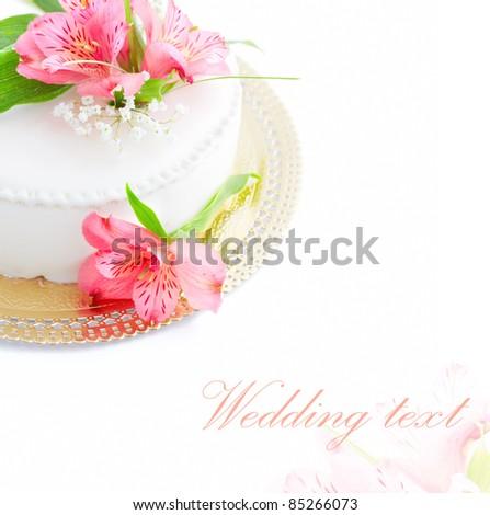 Half of wedding cake with fresh flowers on white background. - stock photo