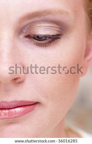 Half of woman face with a makeup macro photo with one eye half-closed