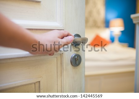 half-open door of a bedroom with hand - stock photo