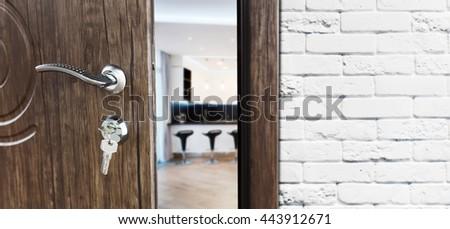 Half opened door to a kitchen. Door handle, door lock. Dining room door half open. Opening door. Welcome concept. Entrance to the room. Door at white brick wall, modern interior design. - stock photo