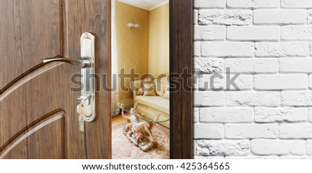 Half opened door to a living room. Door handle, door lock. Lounge door half open. Opening door. Welcome, privacy concept. Entrance to the room. Door at white brick wall, modern interior design. - stock photo