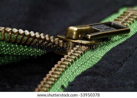 half opened zipper in green and black cloth - stock photo