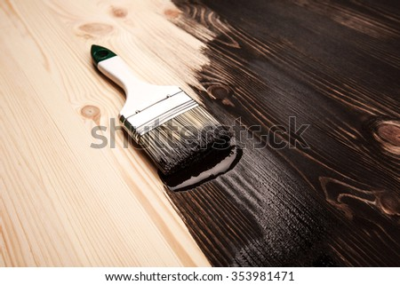 Half painted wooden surface. Black color. Varnishing natural wood with paint brush. - stock photo