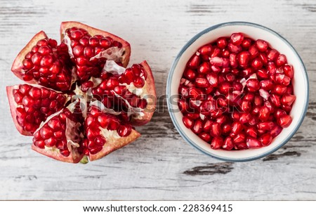 Half pomegranate and pomegranate seeds on a white wooden background - stock photo