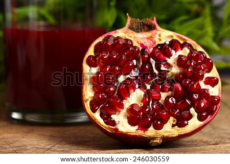 Half pomegranate on wooden table with red juice in the back - stock photo