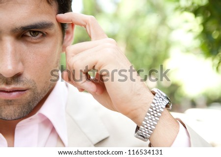 Half portrait close up of a thoughtful businessman's face looking at camera and pointing at his head with his finger. - stock photo