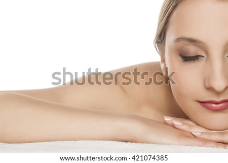 Half portrait of beautiful young woman lying down on towel - stock photo