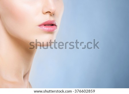 Half portrait of young, beautiful and healthy woman over blue background - stock photo