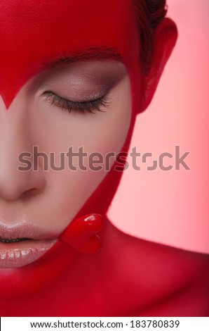 Half portrait of young woman with picture and heart on face and mouth