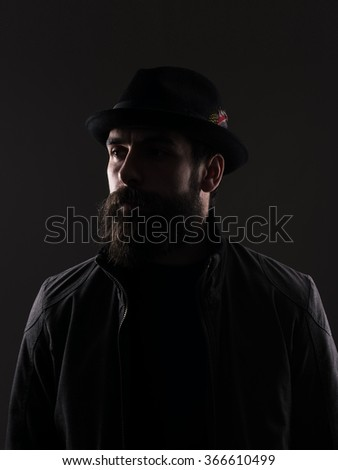 Half profile of serious bearded man in black hat looking away. Low key dark shadow portrait over black background.