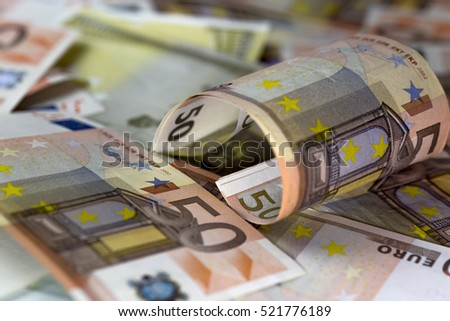 Half rolled fify euro banknote  on  fifty euro banknotes background