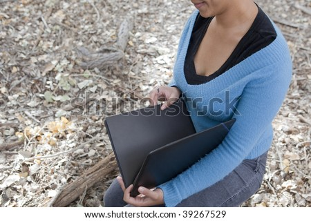 half smiling woman sitting in forest with notebook - stock photo