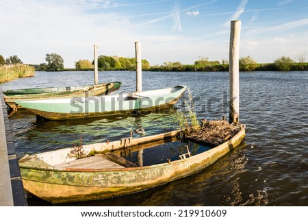 Half sunken abandoned rowing boat filled with water  while grass grows on the deck. - stock photo
