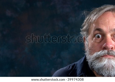Half the face of a bug eyed mature man with beard. - stock photo