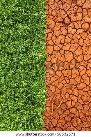 Half the frame is lush green grass and the other half is cracked dry desert sand. Concept of life, growth, moving forward versus death, aridness, stagnation. - stock photo