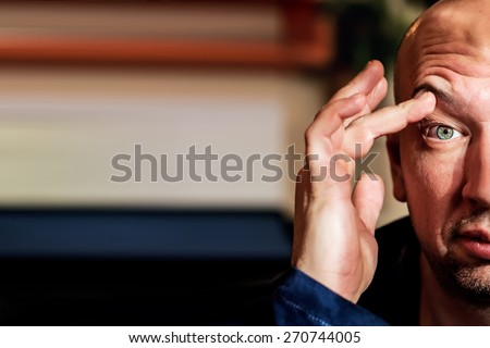 Half view of man is elevating  eyebrow with his hand as he is very sleepy or surprised - stock photo