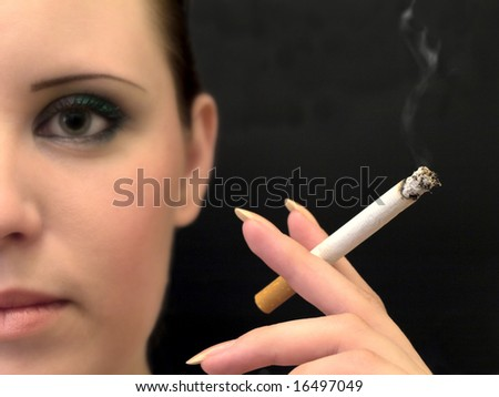 half woman face and hand with cigarette against the black background