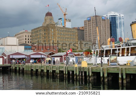 Halifax, Nova Scotia, Canada, August 9, 2014: Touristic harbor waterfront with shops and tourist, gray skies in the background in Halifax, Nova Scotia - stock photo