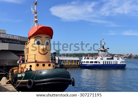 HALIFAX, NS, CANADA - AUG 3, 2015:  Theodore Tugboat, the tour boat inspired by a children's TV show and the Dartmouth Ferry visible at the Halifax waterfront. - stock photo