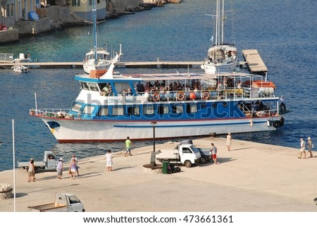 HALKI, GREECE - JULY 20, 2016: Ferry boat Nikos Express docks at Emborio harbour on the Greek island of Halki. The ferry is one of three operating the route between Halki and Kamiros Skala on Rhodes.