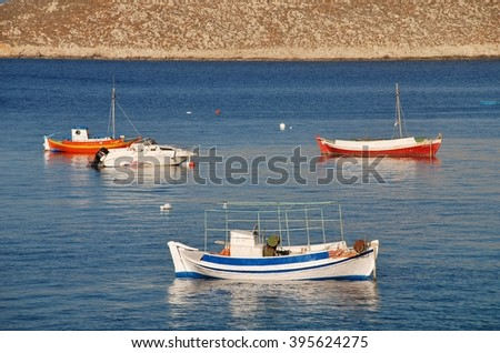 HALKI, GREECE - JUNE 14, 2015: Small boats moored in the late afternoon light at Emborio on the Greek island of Halki. The Dodecanese island derives most of its income from fishing and tourism.
