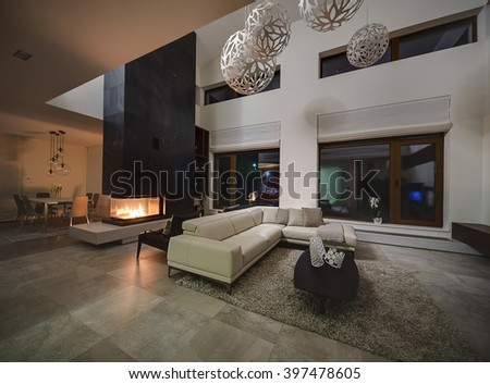 Hall in a cottage with light walls and big round decorative lamps at the top. In the centre there is a beige sofa with pillows and plaid, dark table with three decorative vases, two black armchairs - stock photo