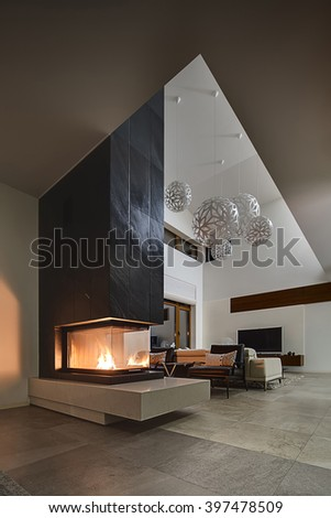 Hall in a cottage with light walls and big round decorative lamps at the top. In the front there is a glass fireplace with burning fire and a black chimney. Behind the fireplace there are two black - stock photo