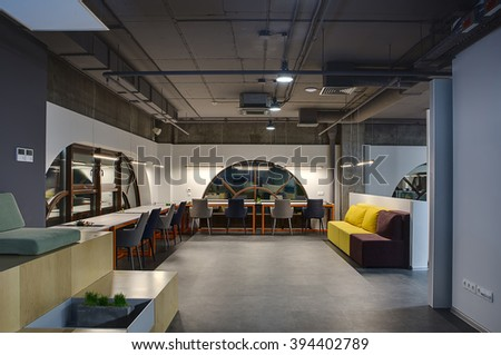 Hall in a loft style with white walls with brown rounded windows. Upper parts of walls are concrete. Close to windows there are light tables with orange legs and gray and blue chairs. Between the - stock photo
