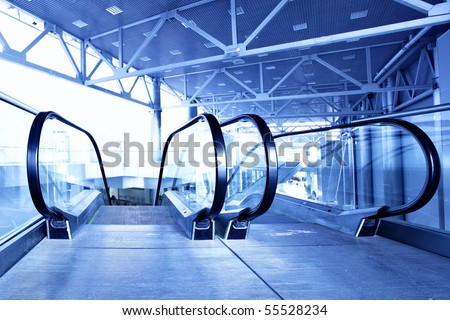 Hall with escalator toned in blue color - stock photo