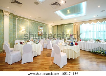 Hall with tables and chairs in a restaurant decorated for a wedding celebration, in place of pictures photo by the author. - stock photo