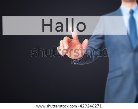 Hallo (Hello in German) - Businessman hand pressing button on touch screen interface. Business, technology, internet concept. Stock Photo