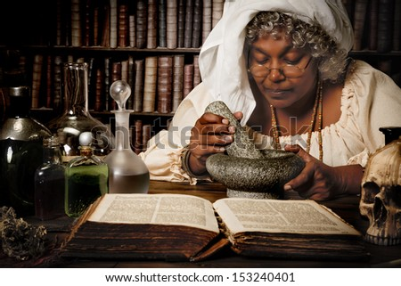 Halloween alchemist working at night with mortar and pestle - stock photo
