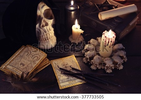 Halloween and magic still life with evil candles, books, skull and the tarot cards. Fortune telling seance or black magic ritual with mysterious occult and esoteric symbols, divination rite  - stock photo