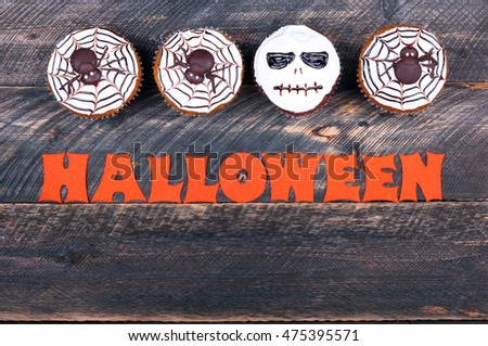 Halloween background. Funny pumpkin muffins with spiders and scull for halloween party on old rustic wooden table. Copy space. Top view