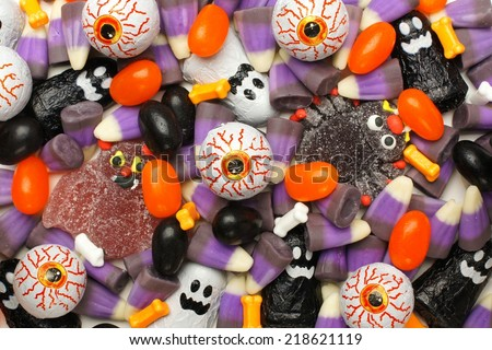 Halloween background of mixed candies, dark color theme - stock photo