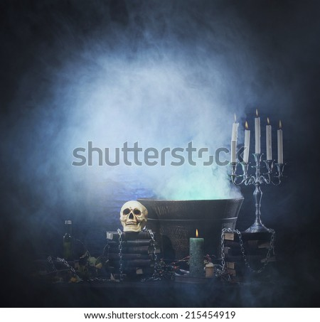 Halloween background with a lot of different witchcraft tools: scull, candles, book, poison and smoke - stock photo